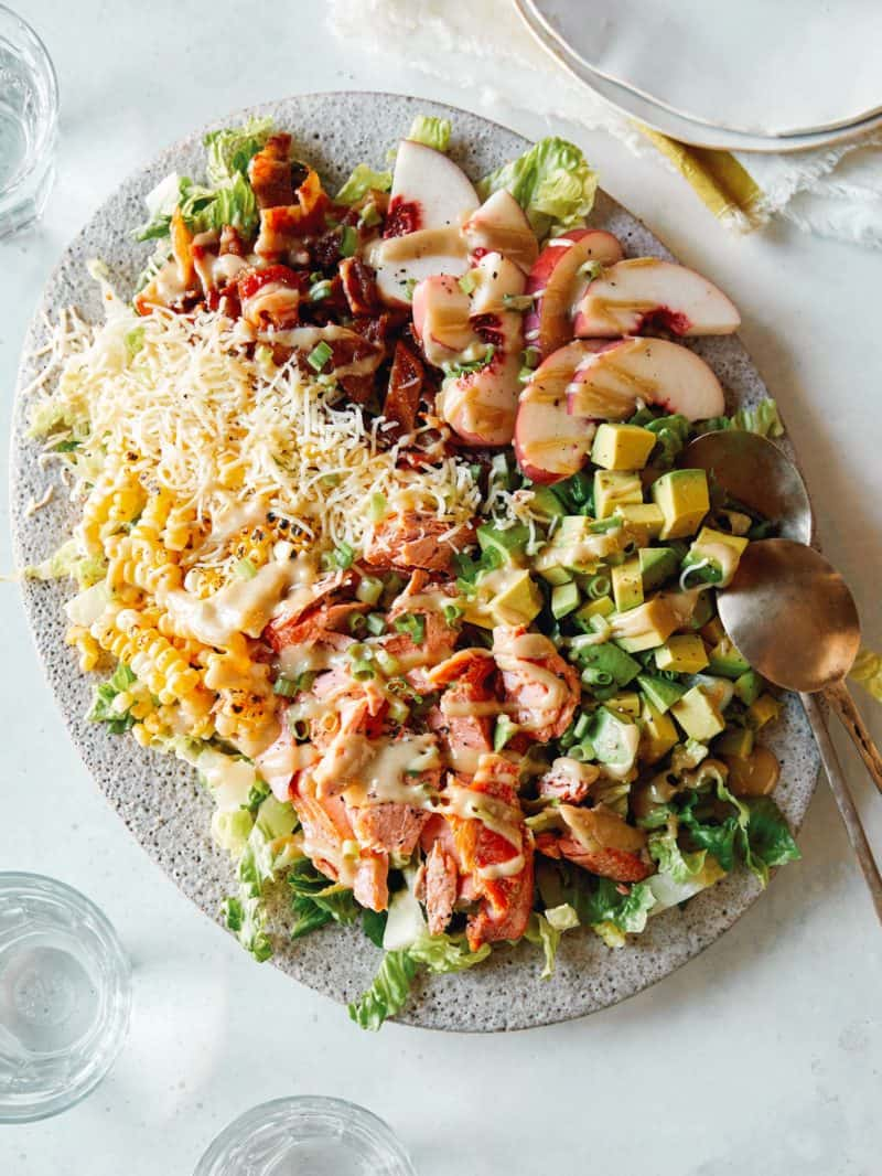 Salmon summer salad on a platter with a spoon.