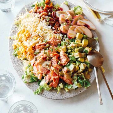 Salmon summer salad on a plate with spoons.