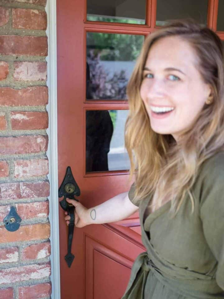 A beautiful blue eyed woman smiling while holding a door handle.