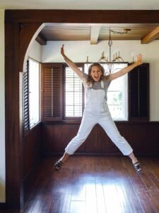 An excited woman jumping in the air with joy in an empty dining room.