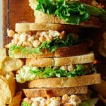 Lined up chickpea salad sandwiches  with potato chips.