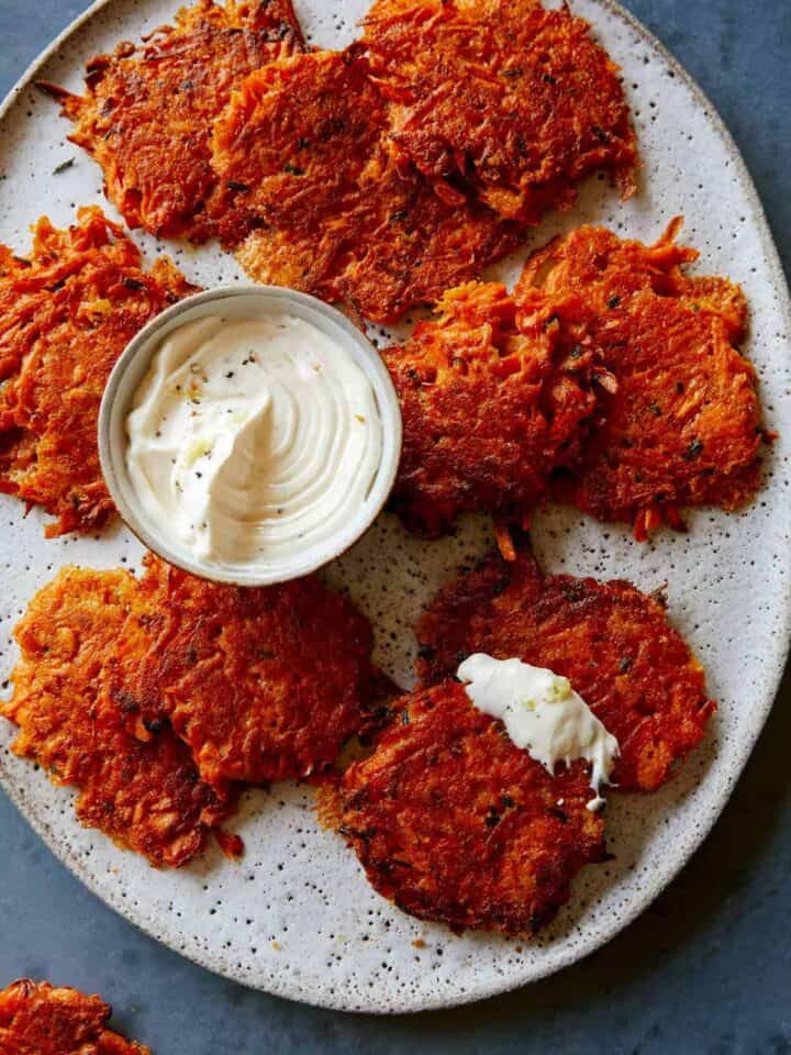 Cheesy sweet potato fritters on a plate with a small bowl of sauce.
