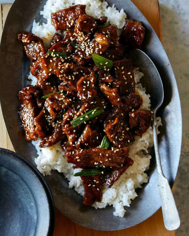 Mongolian Beef recipe in a serving dish over a bed of rice with a spoon in it.