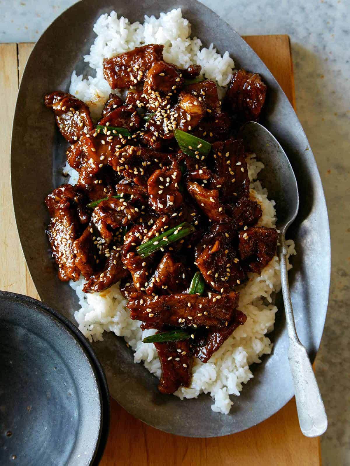 A plate of Mongolian beef on white rice with a spoon.
