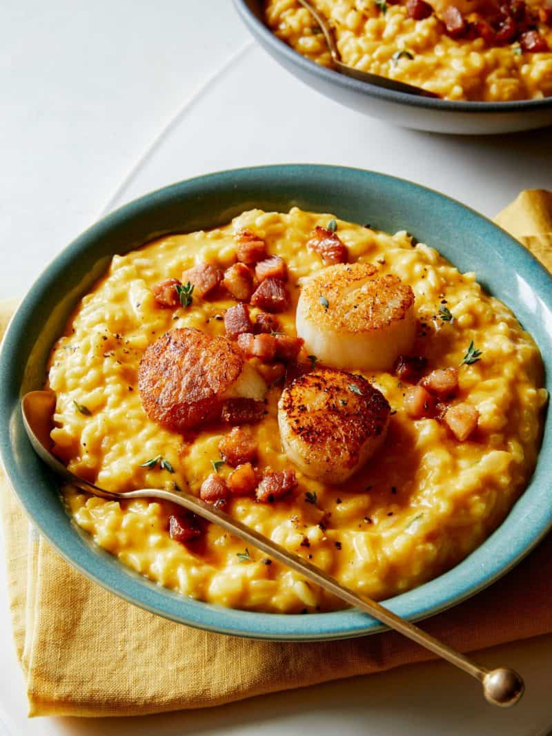 A close up of a bowl of pumpkin risotto with seared scallops and a spoon.