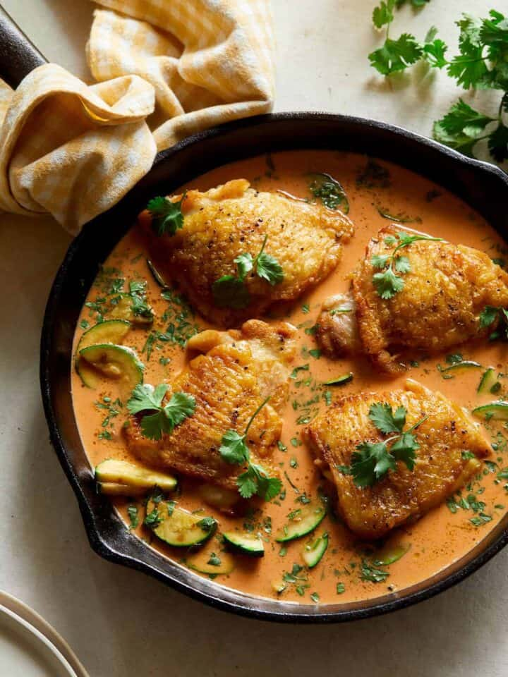 Thai red curry chicken thighs in a pan.