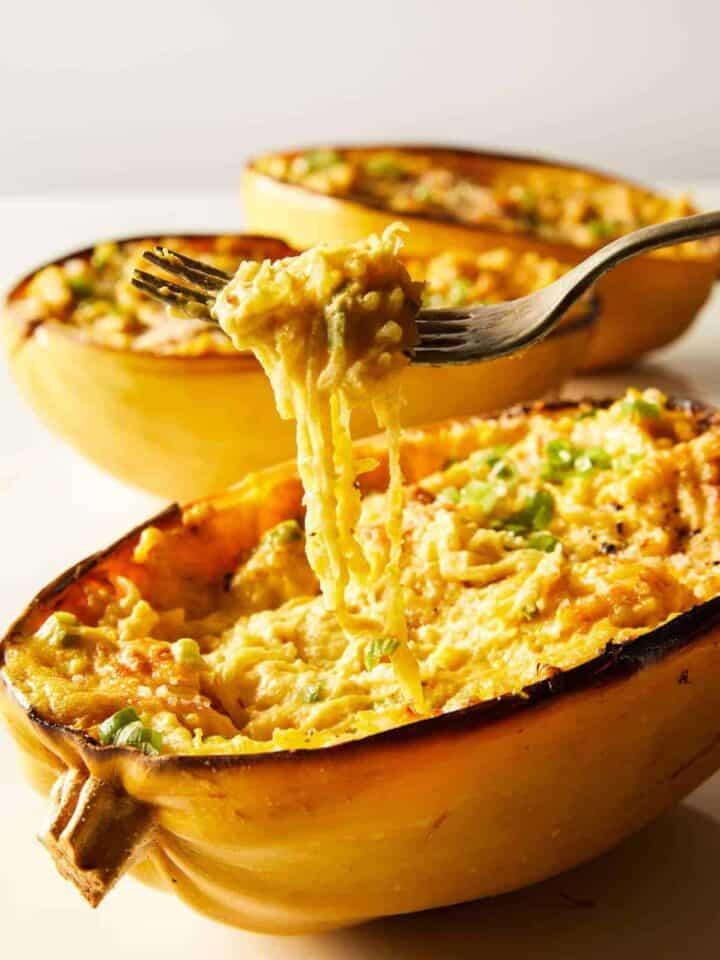 Vegan baked alfredo spaghetti squash with some squash twirled on a fork.