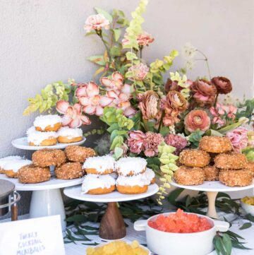 Several cake stands full of doughnuts with a floral arrangement.