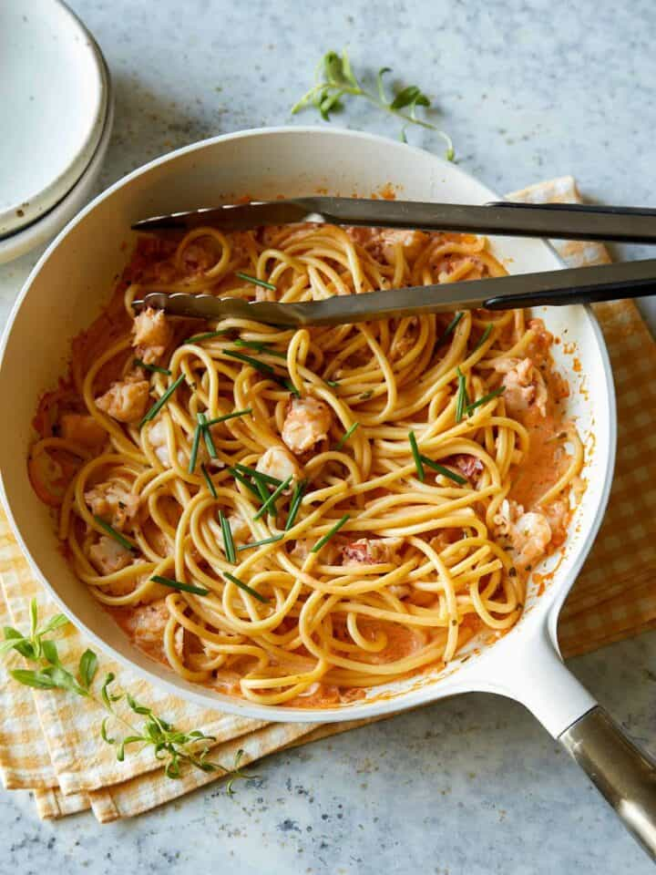 Creamy lobster pasta in a white pot with metal tongs.