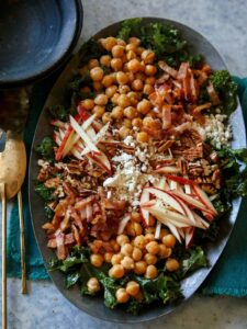 Platter of chicken kale apple and goat cheese salad.