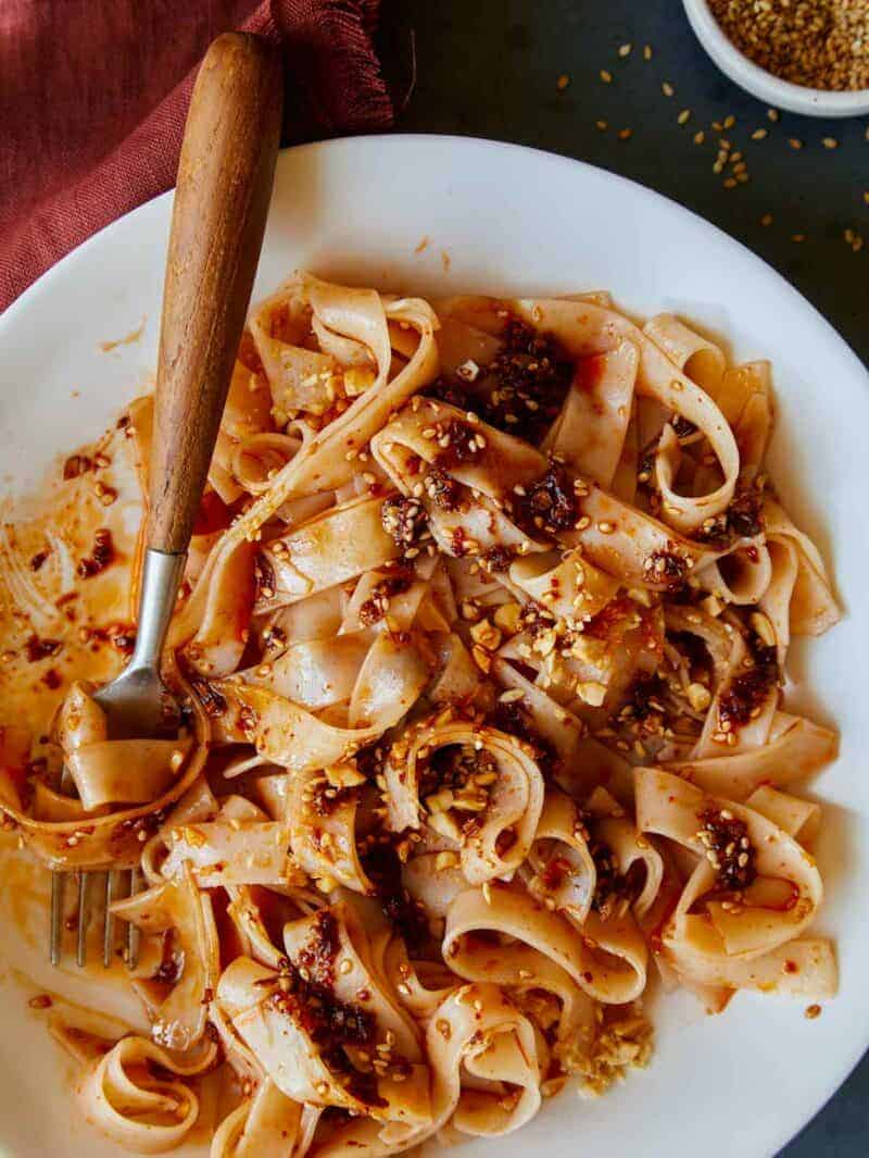 Chili oil garlic noodles on a plate twirled on a fork.