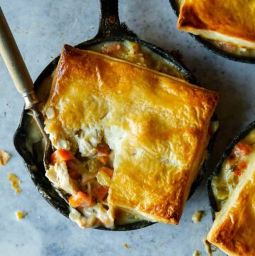 Chicken pot pies in individual skillets with a fork.