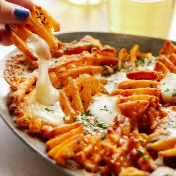 A close up of a hand taking poutine with waffle fries off a plate.