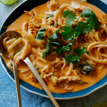Bowl of spicy thai red curry soup with a spoon and fork.