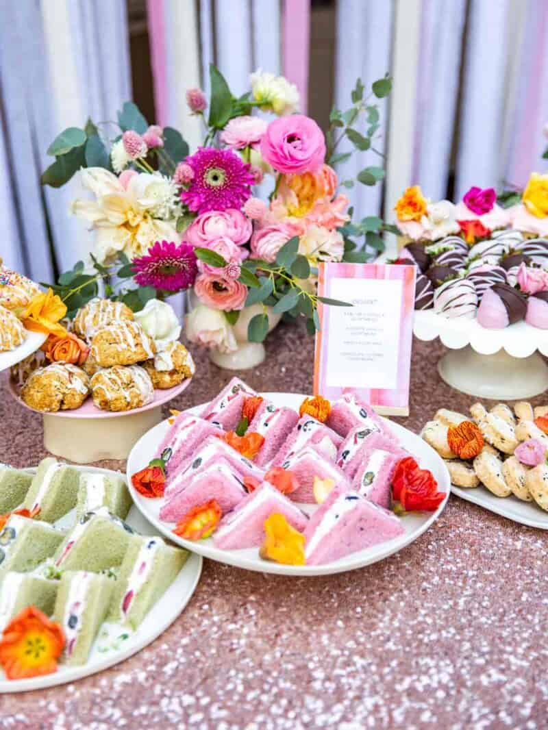 A table full of tea sandwiches and a variety of baked goods with a floral arrangement.