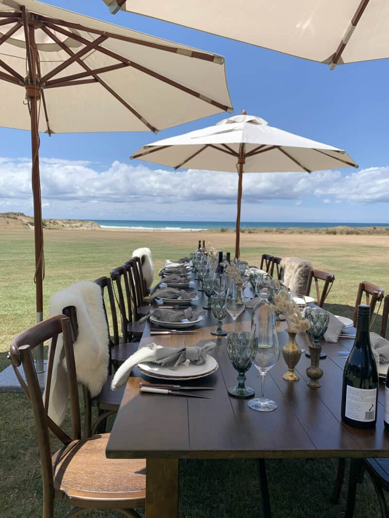 Set table for lunch party outside looking over green fields and ocean.