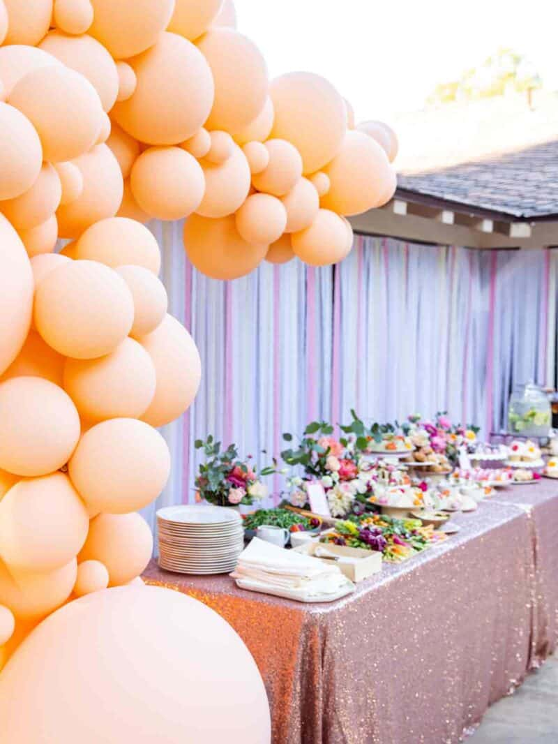 Balloon garland surrounds a table of food.