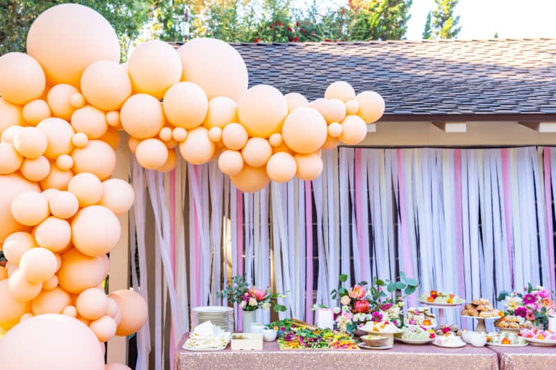 Balloon garland surrounds a table of food with streamer backdrop.