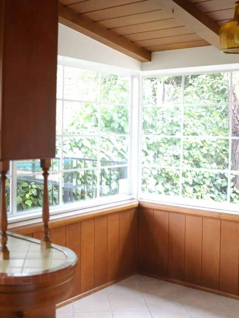 A kitchen breakfast nook with wooden cabinets and windows.