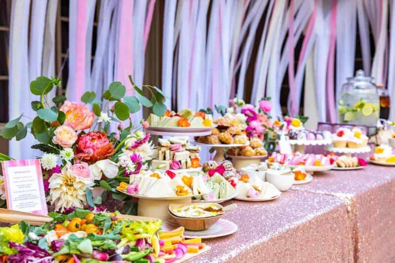 A table full of tea sandwiches and small bites with a floral arrangement.