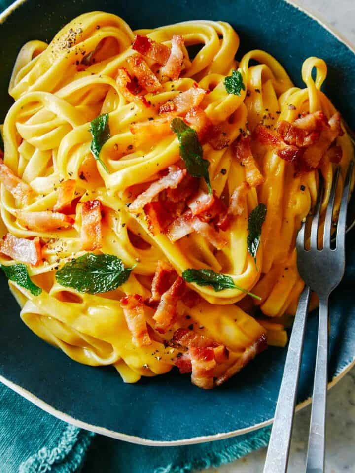 A close up of dairy free creamy butternut squash pasta with a fork.