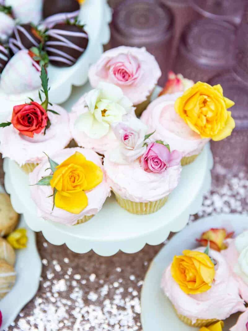 A cake stand with cupcakes covered in edible flowers.