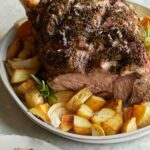 Herb crusted leg of New Zealand grass fed lamb on a plate with potatoes.
