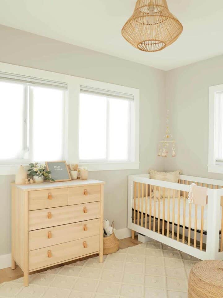Nursery with light colored dresser and crib.