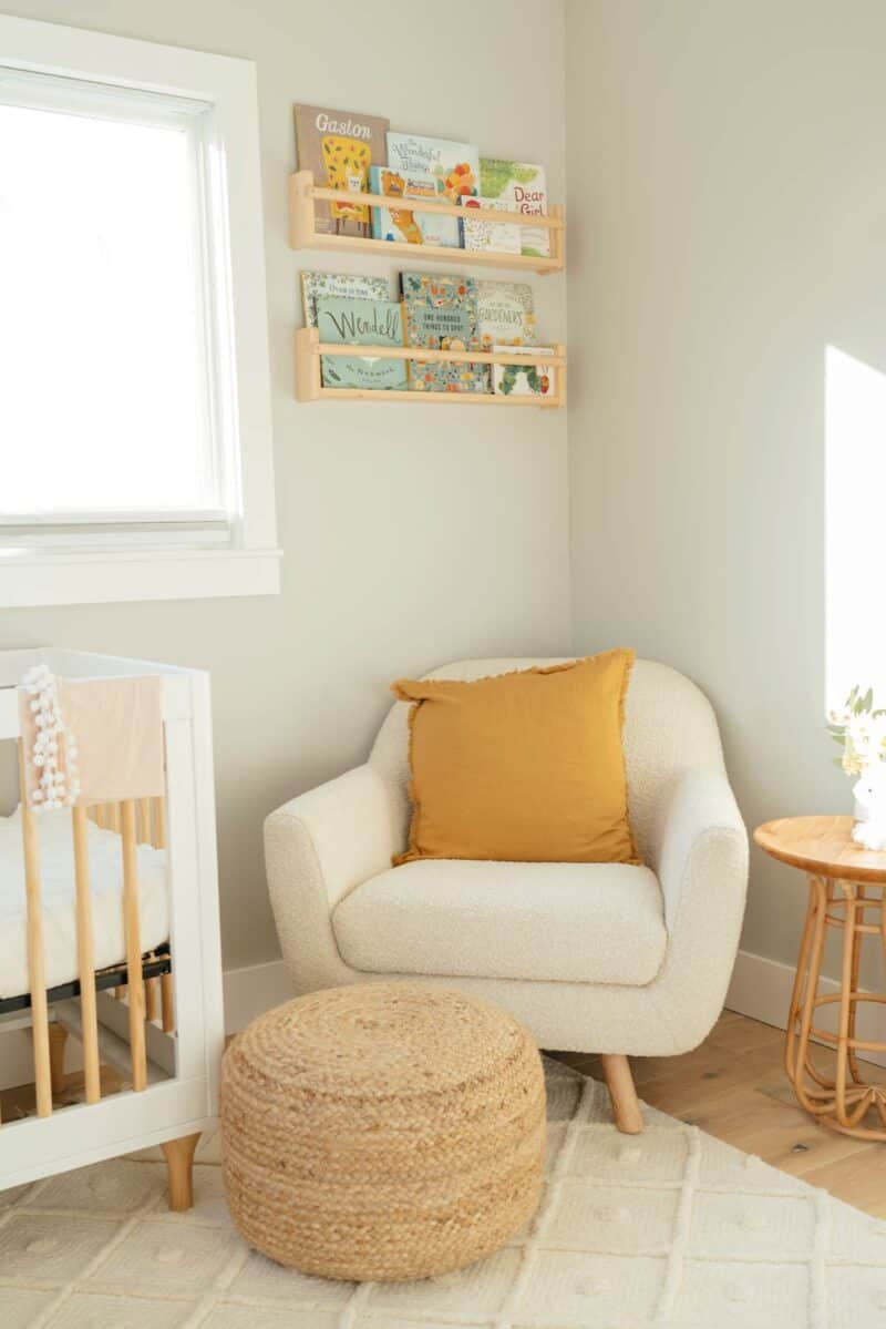 Corner of nursery with shelves and chair.