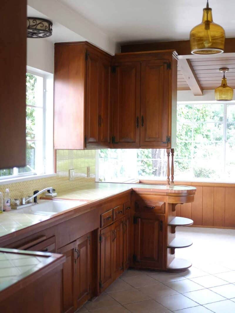 A kitchen sink with wooden cabinets and breakfast nook.