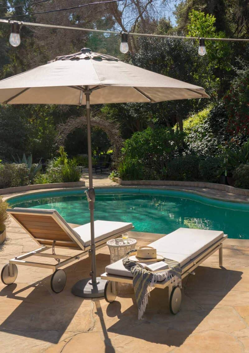Chaise lounges with umbrella by a pool.