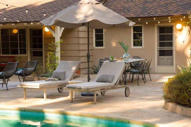 Chaise lounges with umbrella and a dining table by a pool.