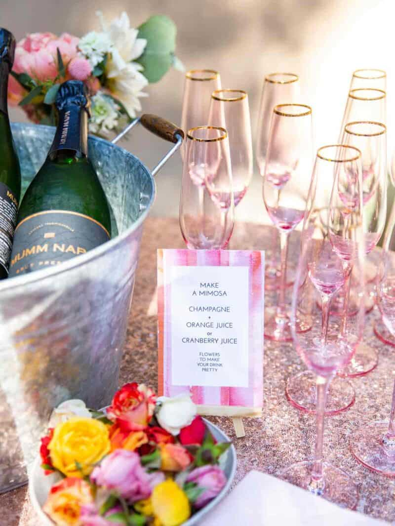 Mimosa bar with champagne bottles, pink glasses, and a sign.
