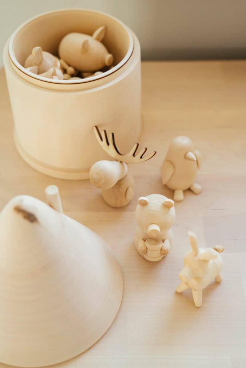 A variety of small wooden animals in and out of container.