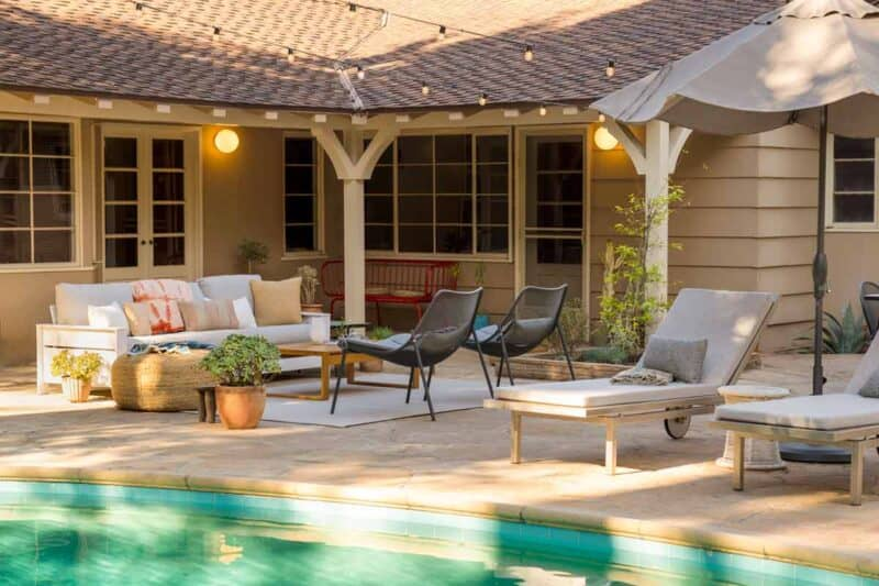 A furnished patio with a couch, chairs, and chaise lounge by a pool.