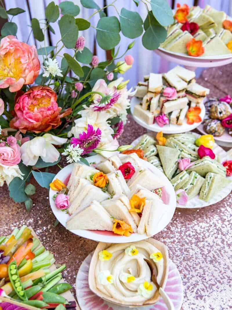 A table full of tea sandwiches and a floral arrangement.