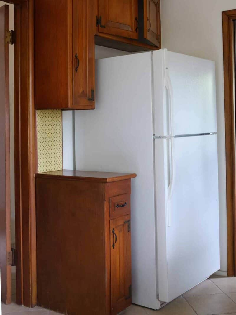 A refrigerator next to wooden cabinets.