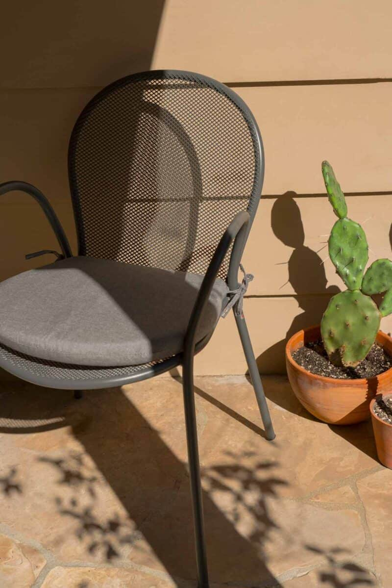 Outdoor chair next to a cactus.