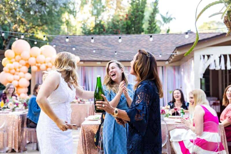 A group of beautiful, smiling women with a sabered champagne bottle in hand.