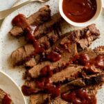 Sliced slow cooker BBQ Wagyu beef brisket with sauce drizzled and on the side.