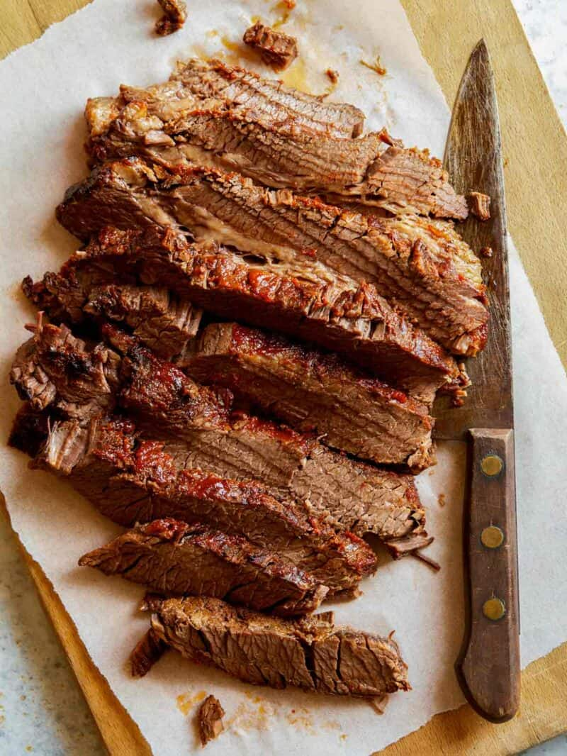 Slow cooked BBQ Wagyu Beef brisket sliced on a cutting board with a knife.