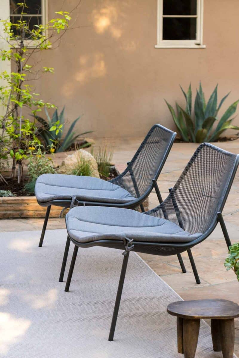 Two patio chairs with garden.