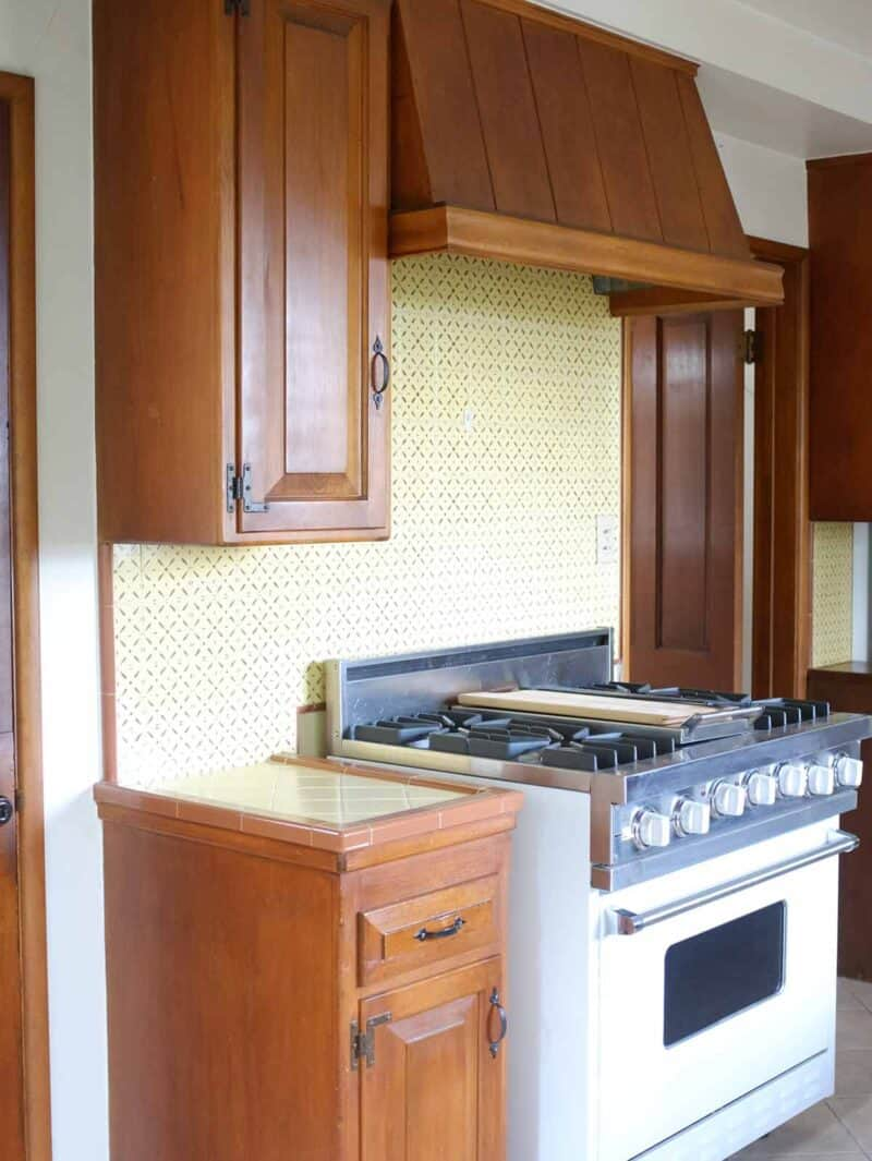 A stove top oven with wooden cabinets.