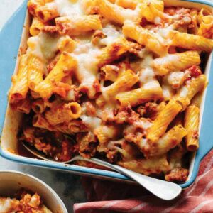 Baked Ziti in a blue pan with a spoon.