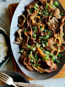 Korean beef bulgogi on a platter with a side of white rice.