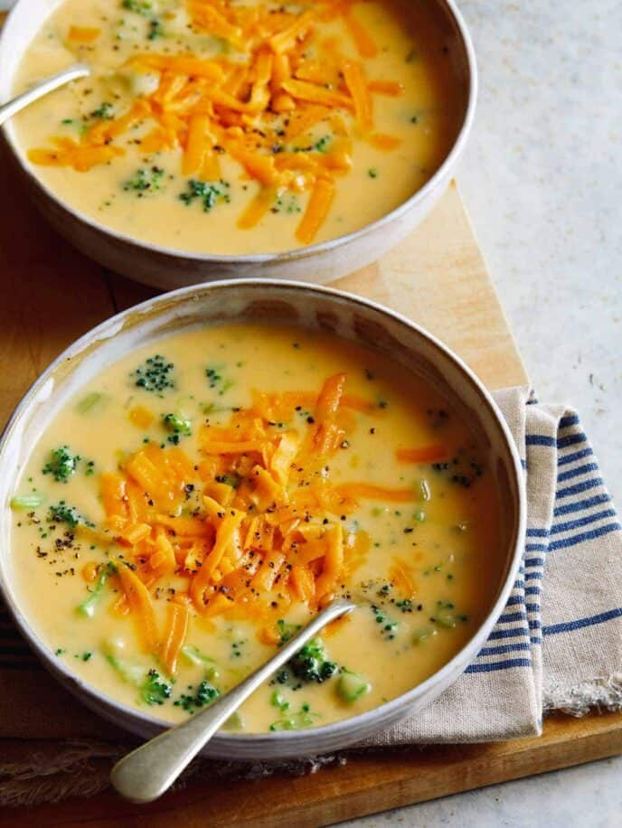Bowls of broccoli cheddar soup with a spoon.