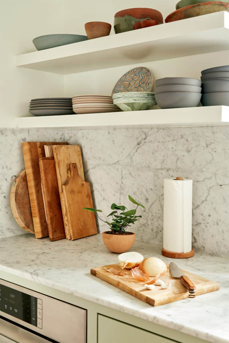 Floating shelves with plates and bowls over a marble backsplash and countertop.