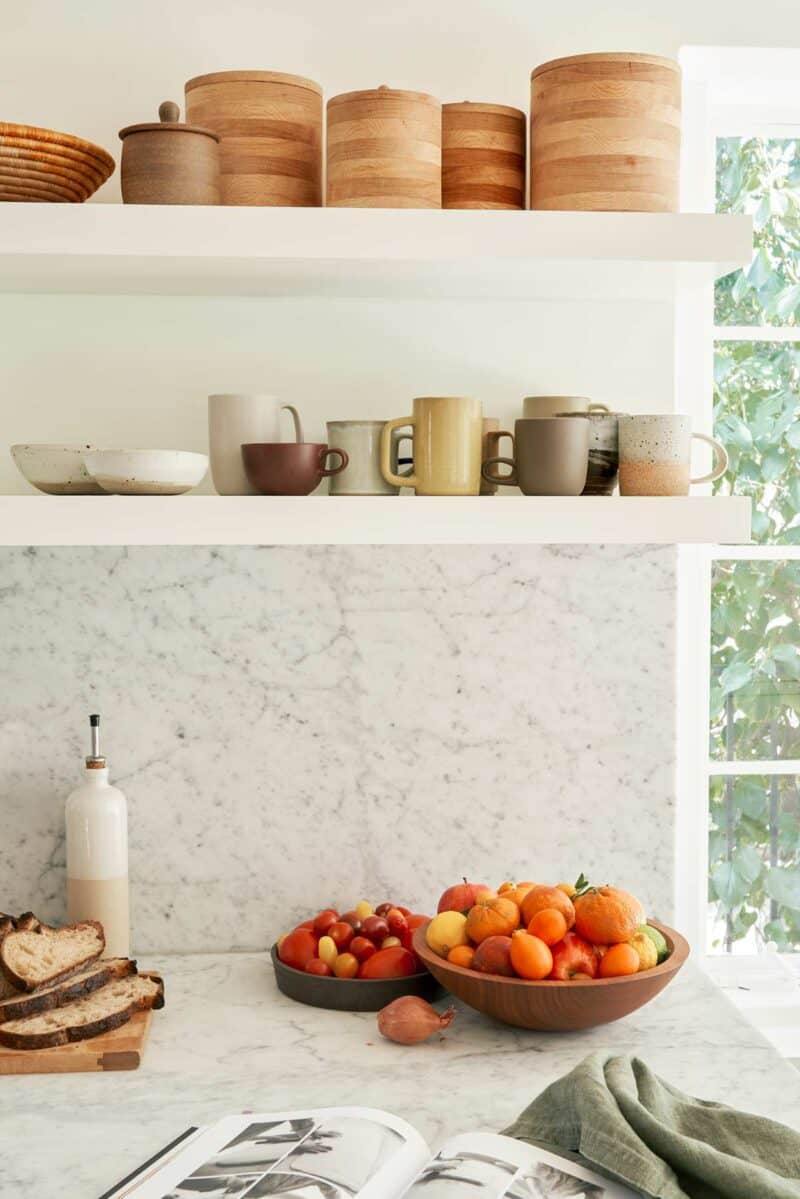 Floating shelves with mugs over a marble backsplash and countertop.