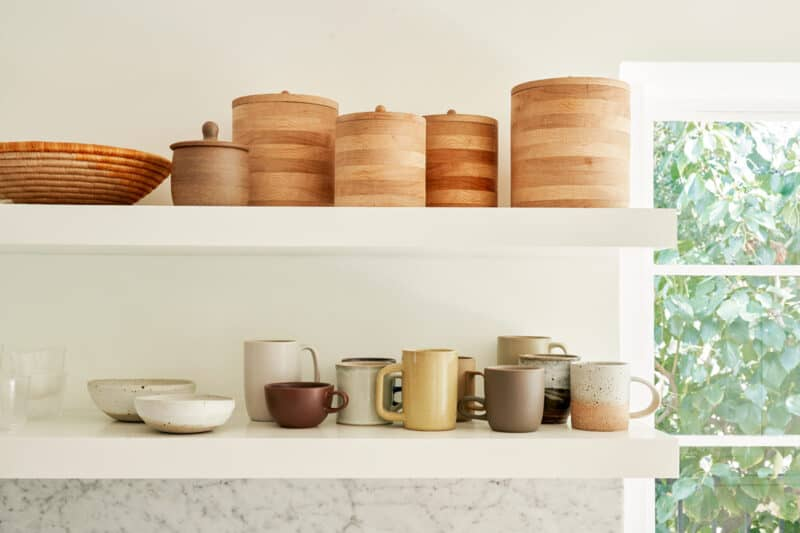 Floating shelves with a variety of containers and mugs.