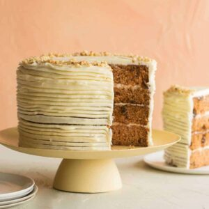 A recipe for Carrot Cake with Cream Cheese Frosting on a pedestal with a slice taken out, a plate to the right with the slice on it. The cake is three layers.